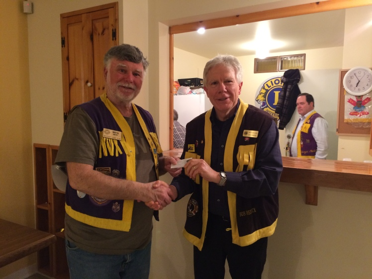 Lion Bob Reddick (right) presents Lion President Wayne Bent with the Silver Centennial Lion pin for recruiting and retaining new Lions for 2017.